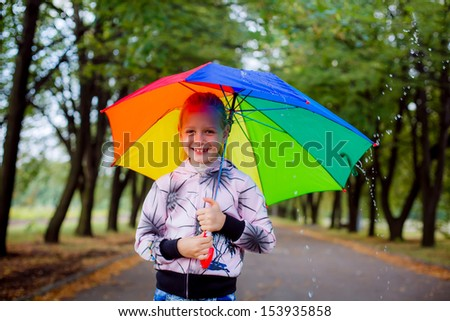 beautiful blond girl in the bright umbrella - stock photo
