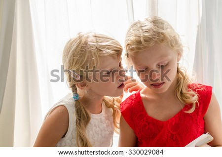 beautiful blond girl in white and red dresses sitting together and speaking - stock photo