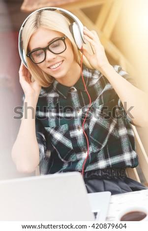 Beautiful blond girl is enjoying wonderful melody - stock photo