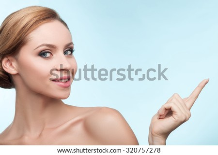 Beautiful blond girl is pointing her finger sideways. She is standing and smiling. The naked lady is looking at the camera with happiness. Isolated and copy space in right side - stock photo