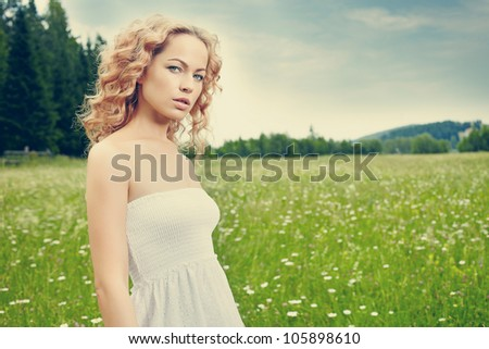beautiful blond girl on green field with flowers. Rural scene - stock photo