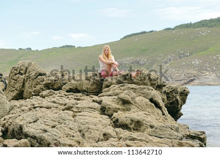 beautiful blond girl on rockey beach - stock photo