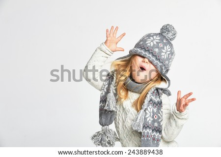 Beautiful blond girl playing in the winter warm hat and scarf on a white background - stock photo