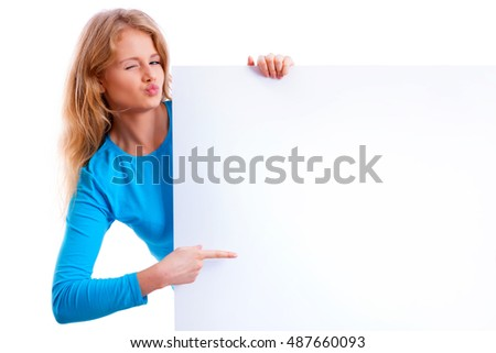 beautiful blond girl pointing at an empty white board and sending a kiss
