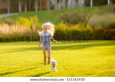 beautiful blond girl running in the park on a glade with a dog - stock photo