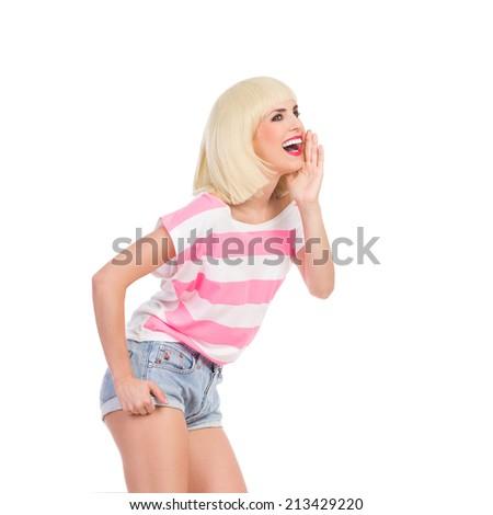 Beautiful blond girl shouting. Three quarter length studio shot isolated on white. - stock photo