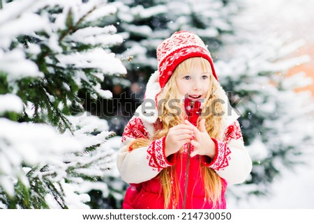 Beautiful blond girl standing in a snowy forest