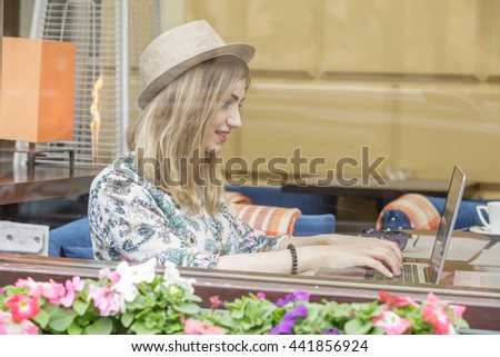 Beautiful  blond girl using laptop in the cafe. She is smiling. View from behind the glass of cafe. On the glass reflection of city objects.