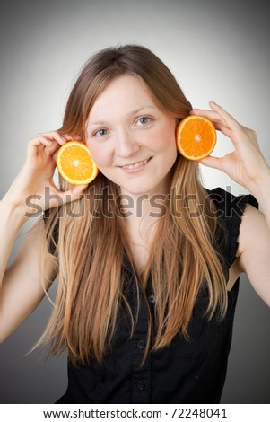 beautiful blond girl using orange as earrings, with grey background - stock photo