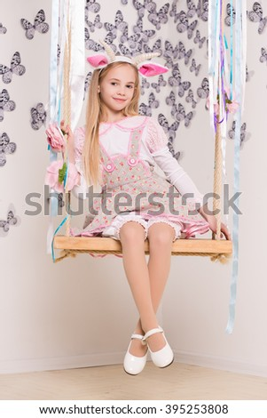 Beautiful blond girl wearing goat costume posing on the swing - stock photo