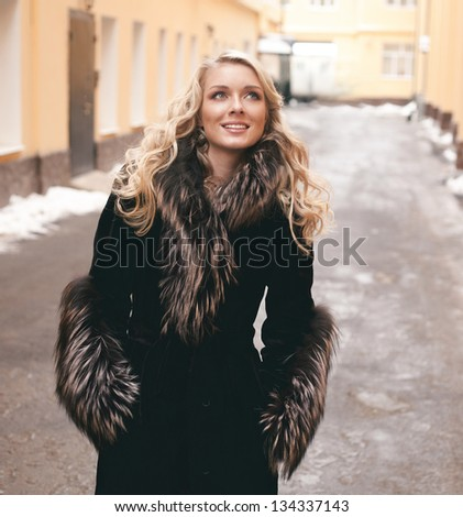 Beautiful blond girl wearing winter coat on the street back yard background