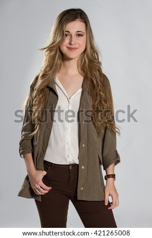 Beautiful blond girl with blue eyes on a white background. She wears jacket and brown pants and white shirt.