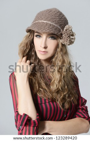 beautiful blond girl with curly hair in cap , portrait - stock photo