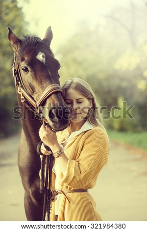 beautiful blond girl with long hair hugging a horse in autumn colors - stock photo