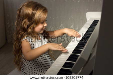 beautiful blond girl with  lounge curl playing a piano in apartment - stock photo