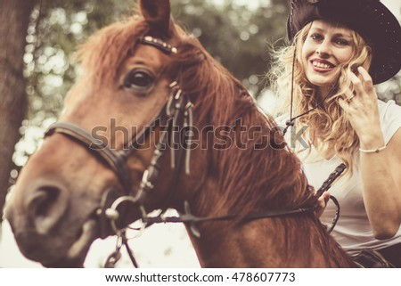 Beautiful blond hair lady with brown horse