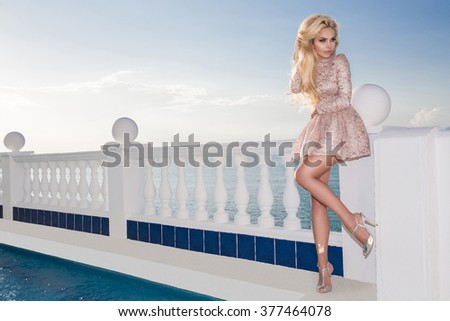 Beautiful blond hair sexy woman in an elegant gold short dress standing at the railing at the swimming pool - stock photo