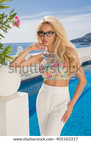 Beautiful blond hair sexy woman young girl model in sunglasses and elegant color  with crystals sweatshirt, top around the pool with a balustrade overlooking the sea and the island of Santorini