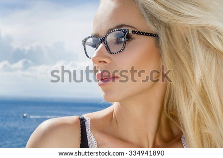 Beautiful blond hair sexy woman young girl model in sunglasses and elegant white and black sexy swimsuit lingerie with crystals around the pool with a balustrade