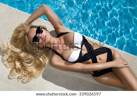 Beautiful blond hair sexy woman young girl model in sunglasses and elegant white and black sexy swimsuit lingerie with crystals around the pool