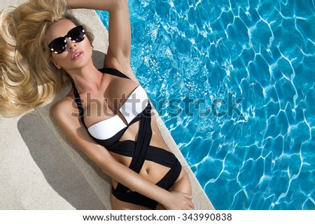 Beautiful blond hair sexy woman young girl model in sunglasses and elegant white and black sexy swimsuit lingerie  around the pool with a balustrade  - stock photo
