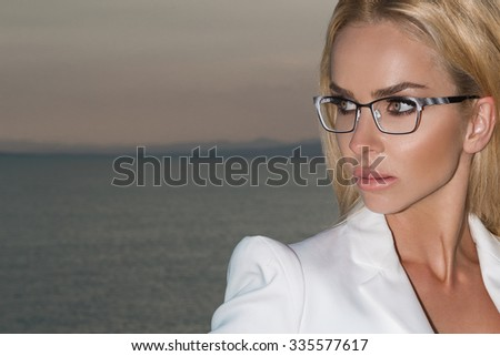 Beautiful blond hair sexy woman young girl model in sunglasses in white elegant jacket, suit around the pool with a balustrade overlooking the sea and the island of Santorini