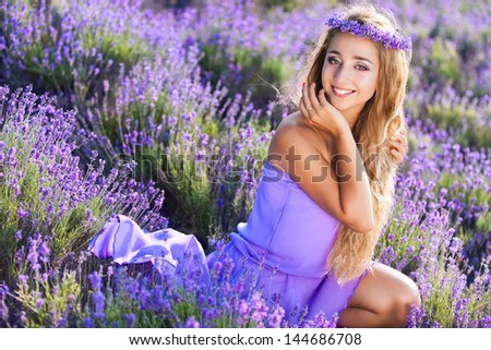 Beautiful blond hair woman in lavender meadow - stock photo