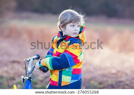 Beautiful blond kid boy biking on his bicycle and having fun on cold  day, outdoors. Active leisure with children in winter, sping or autumn. - stock photo