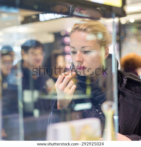 Beautiful blond lady testing and smelling perfume in a beauty store. Woman buying cosmetics in perfumery. - stock photo
