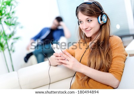 Beautiful blond listening to some music while her boyfriend is bored - stock photo