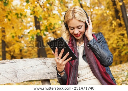 Beautiful blond listens to the music through a digital tablet. Selective focus on face.