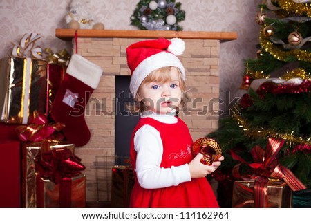 Beautiful blond little girl in a red Christmas hat posing by the fireplace on Christmas Eve, enjoys gifts. A series of photos in my portfolio.