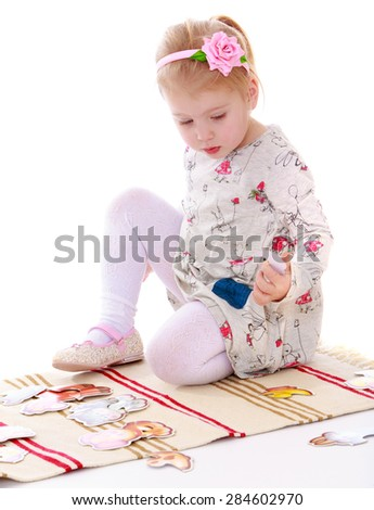 Beautiful blond little girl sitting on the rug and plays- isolated on white background - stock photo