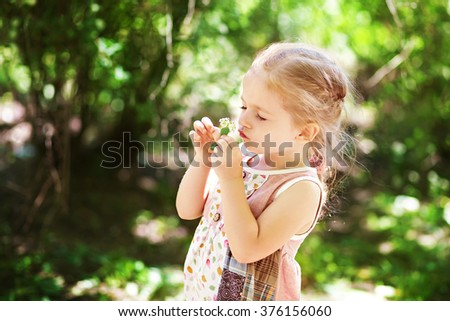 Beautiful blond little girl smelling flower