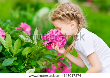 Beautiful blond little girl with long hair smelling flower - stock photo