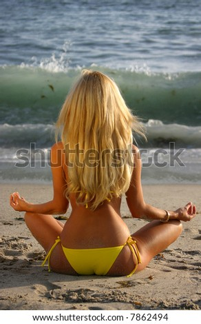 Beautiful Blond Meditating on the beach at Sunset