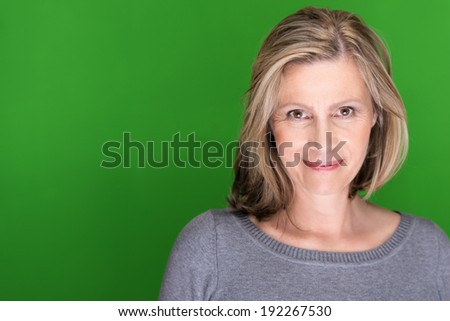 Beautiful blond middle-aged woman smiling in pleasure looking at the camera against a green background with copyspace - stock photo