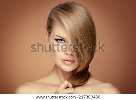 Beautiful blond model holding her long straight hair looking at camera.  - stock photo