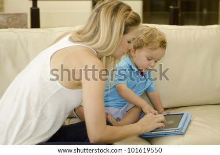 Beautiful blond mother playing with her son and a tablet