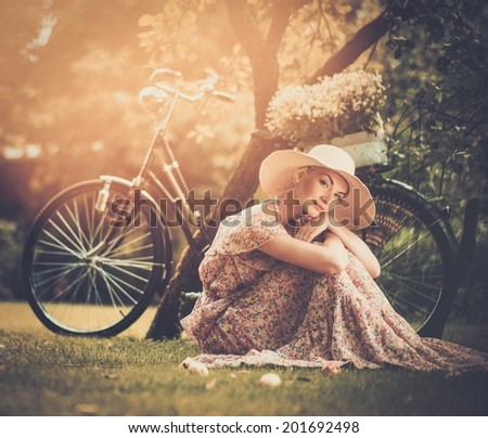 Beautiful blond retro woman with bicycle behind her - stock photo