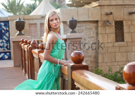 Beautiful blond russian professional model girl having joy and relax in luxury spa resort in tropical country on windy sunny summer day - stock photo