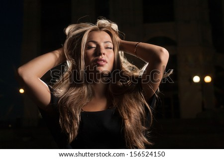 Beautiful blond 20s female posing alone outside at night with hands in her beautyful hair - stock photo