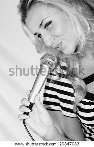 Beautiful blond standing with microphone in her hands