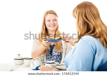 Beautiful blond teen girl having a tea party with her mother.  Isolated on white.   - stock photo