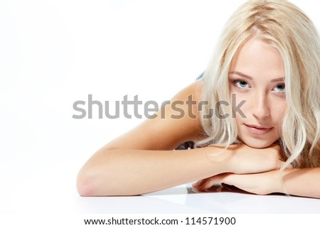 Beautiful blond teen girl lying and looking at camera. Isolated on white background