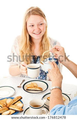 Beautiful blond teenage girl being served at a tea party.  Isolated on white.   - stock photo