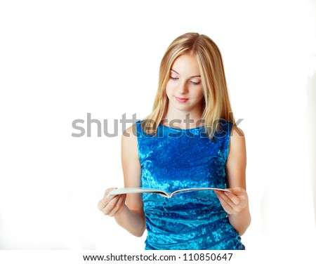 beautiful blond teenage girl reading fashion magazine on white background
