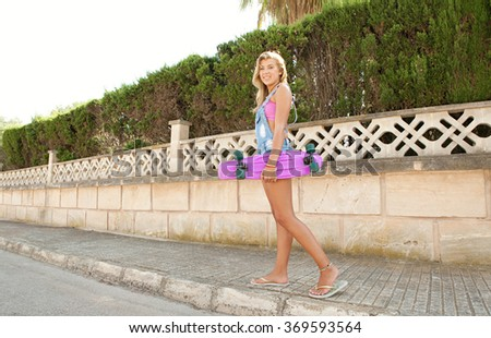 Beautiful blond teenager girl smiling looking at camera, walking in a suburban street holding a skateboard on a sunny day, outdoors. Adolescent lifestyle sporty living activities, home exterior.