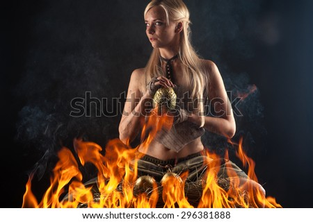beautiful blond with a dragon egg in hands in the fire