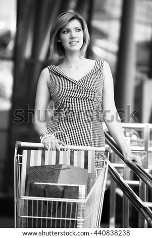 Beautiful blond with shopping cart  - stock photo